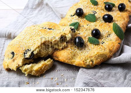 A piece of Italian bread Focaccia with olive and herbs. Homemade traditional Italian bread focaccia.