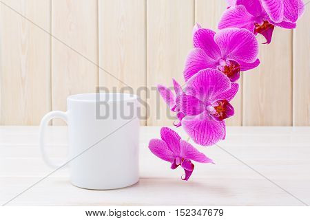 White coffee mug mockup with pink orchid. White coffee cup mock-up for brand promotion. Empty mug mockup for design presentation.