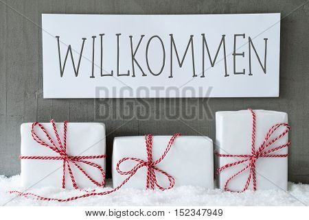 Label With German Text Willkommen Means Welcome. Three Christmas Gifts Or Presents On Snow. Cement Wall As Background. Modern And Urban Style. Card For Birthday Or Seasons Greetings.