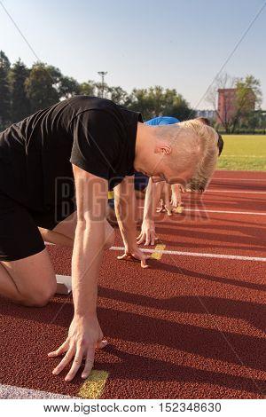 Athletic man starting evening jogging in sun rays