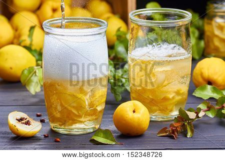 carbonated drink with syrup of japanese quince on fresh quince fruits background over dark wooden table