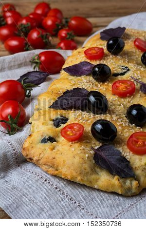 Italian bread focaccia with olive basil and cherry tomato. Homemade traditional Italian bread focaccia on the linen napkin.