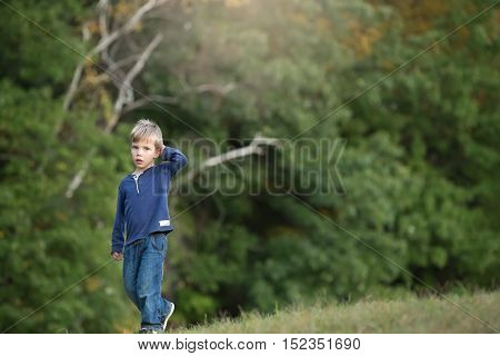 portrait of a sad blonde boy walking alone and sad in the woods