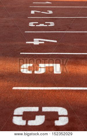 Red race track with numbers on sunny morning