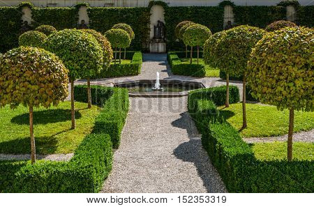 Augsburg, Germany - September 08, 2016: Formal manicured public garden with topiary in Augsburg, Bavaria, Germany with a path leading to a small pond and fountain between a row of trimmed trees