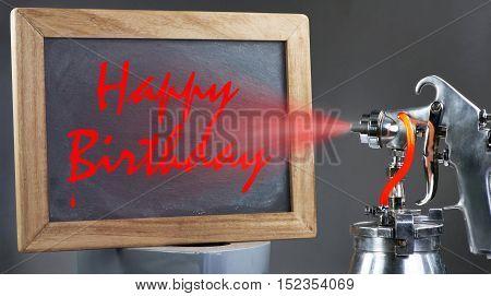 Spray painting happy birthday on a blackboard.