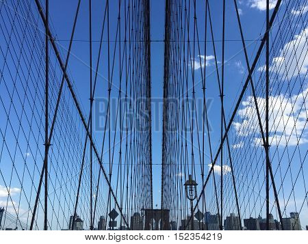 The symmetry of the Brooklyn bridge cable-stayed and buildings with blue sky, New York