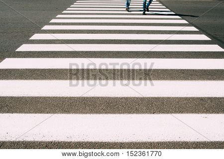 Crossroad with walking people background. Pedestrian zebra on asphalt close-up photo. City street, busy people, safe road crossing concept