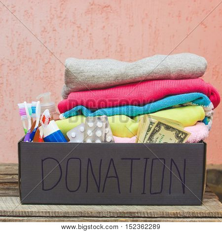 Donation box with clothes, living essentials and money. Toned image.