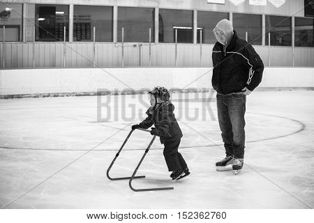 Four year girl with her father learning how to skate on ice at a hockey rink in black and white