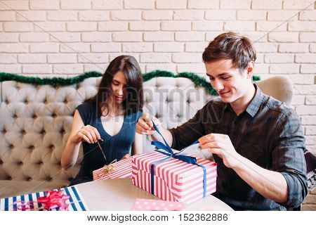 Happy couple unpacking xmas presents. Young happy man and woman giving gifts to each other. Christmas Eve, joy, winter holiday concept