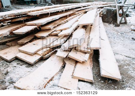 Bunch of boards covered with snow. Frosted wooden planks left outside in winter. Cold, early frosts, hoar concept