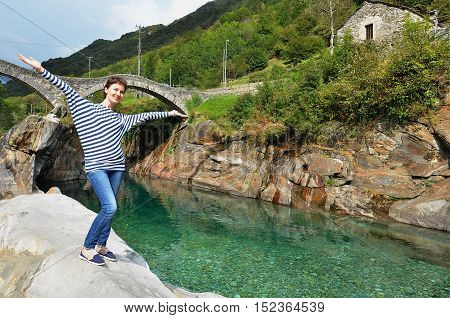 Happy woman rising hands on the clear Verzasca river background, Switzerland. Travel concept