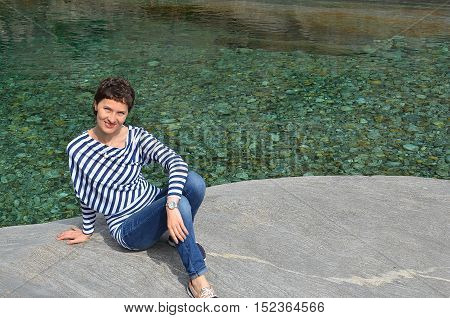 Happy young brunette woman sitting on a rock, clear Verzasca river background. Travel concept