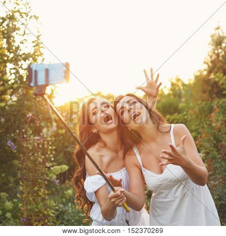 Two cute sisters make fun selfie. Girls fooled. They are singing. Family fun. Social networks.