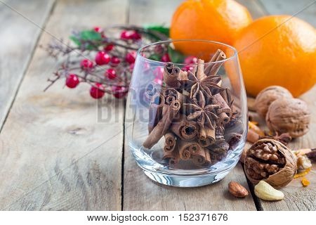 Cinnamon sticks and anise stars in glass with oranges and nuts on background fall winter decoration copy space