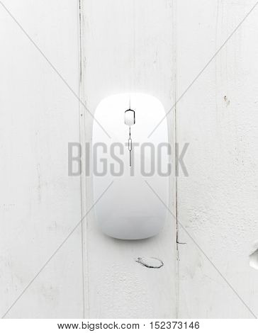 White computer mouse with pad on a wooden background, top view