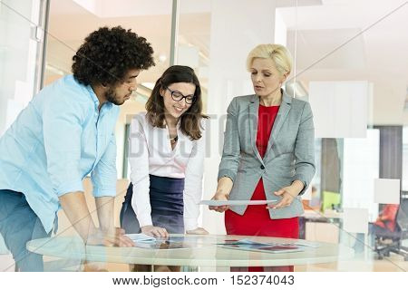 Mature businesswoman with colleagues discussing over project at table in office