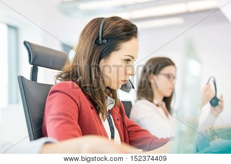 Young businesswoman using headset with female colleague in background at office