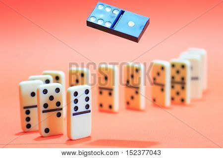 White dominoes standing in a row on red background. One black domino above