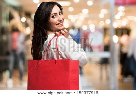 Smiling woman holding a shopping bag in a shopping mall