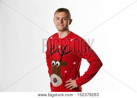 Caucasian man with hand on hips whilst wearing a christmas jumper looking to camera