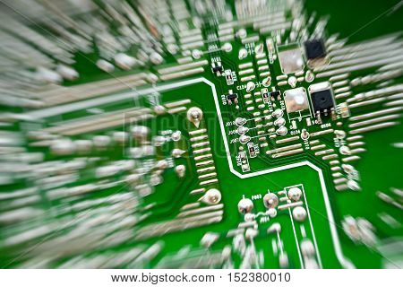 green circuit board representative of the high tech industry and computer science top view radial blur effect center off-side.