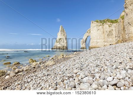 Daytime long exposure shot of pinnacle rock and natural arch at the cliffs of Etretat, Normandy, France