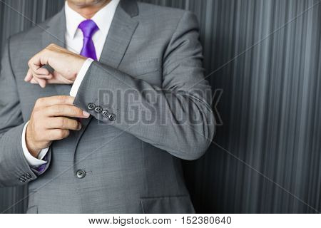 Close up view of business man adjusting his cufflinks and wearing a lovely tie