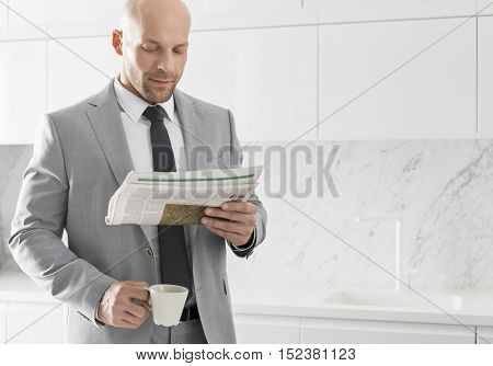 Bald business man reading newspaper in the morning