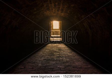 Basement interior with stone floor - Medieval European basement interior with round ceiling and stone floor with strong sun lights at the entrance