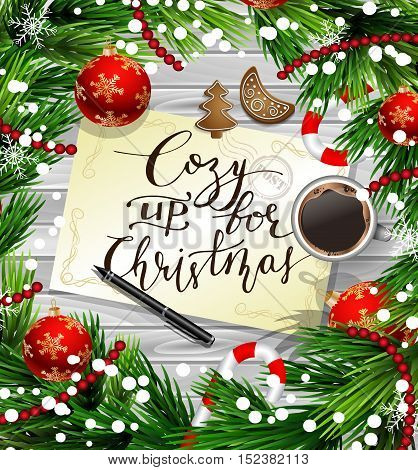 Christmas New Year design wooden background with christmas decorations candy canes snow and balls arranged in a frame with handwritten Cozy up for Christmas a cup of coffee gingerbread cookies and a pen in red.