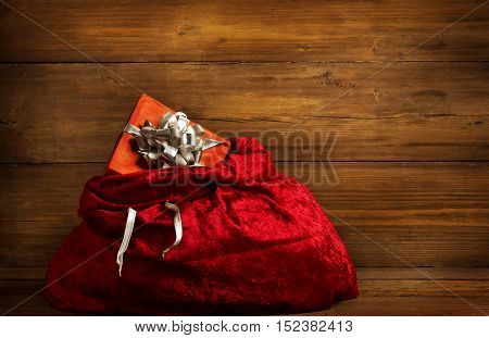 Santa Claus Bag Full By Present Gift Box Red Christmas Sack on Brown Wood Wall Background