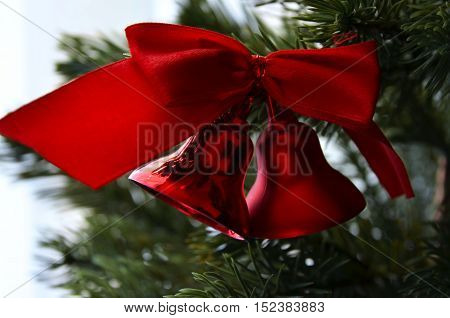 Close up of Fir tree branch and traditional large glitter red bells and bow. Christmas or New Year concept. Winter festive background.