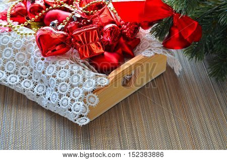 Fir tree branch and traditional decoration: snowflake red bells heart cone on wood box with snow white napkin. Christmas or New Year concept. Winter festive background.
