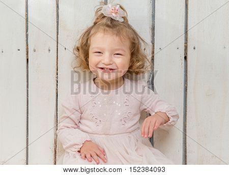 funny stylish little girl in fluffu skirt sitting on the floor in wooden studio