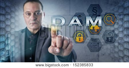 Experienced male data manager is pushing DAM on a touch screen. Information technology concept and data security metaphor for Database Activity Monitoring which is data protection technology.