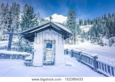 Alpine rustic chapel in winter decor - Picturesque snowy scenery in the Austrian Alps with an old chapel surrounded by an aged wooden fence a fir forest and mountain peaks covered in snow.