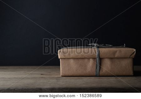A gift box in plain brown paper wrapping with dark grey raffia ribbon on oak table with black chalkboard background providing copy space.