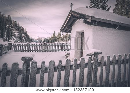 Vintage chapel in winter settings - Winter scenery with a small rustic chapel covered with snow surrounded by a wooden fence and snowy trees. Image captured in Ehrwald Austria.