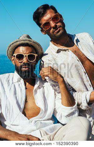 Portrait of two stylish bearded man in sunglasses wearing unbuttoned shirts
