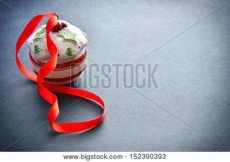 Vintage Christmas red and white ball with ribbon on black background. Winter festive decoration.Copyspace