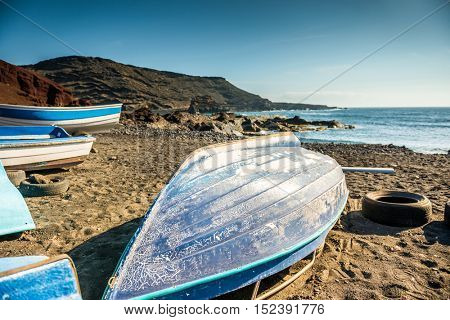 inverted wooden fishing boat on the shore of Lanzarote bay, Canary island, Spain