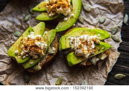 Sandwich with Avocado black unleavened bread mozzarella cheese sprinkling spices and pumpkin seeds on over dark wooden textured background. Healthy eating theme.
