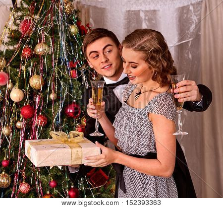 Couple on party drinking champagne near Christmas tree. Love and champagne.