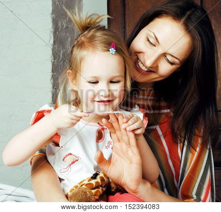 mother with daughter together in bed smiling, happy family close up, lifestyle people concept, cool real modern family, reacreational