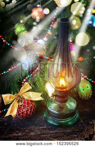 vintage glowing lantern with decorated christmas evergreen wreath, low key with glimming lights
