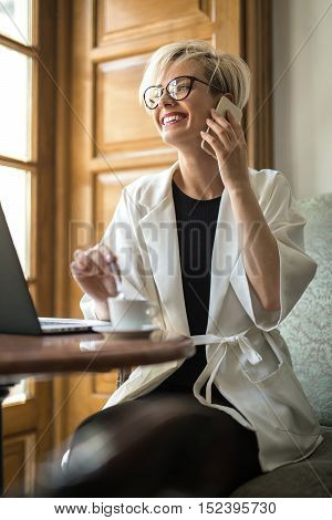 Joyous blonde girl in glasses sits on the armchair at the table with laptop in the cafe and talks on the cell phone. She puts the spoon in the white cup. Woman wears black dress and a white cloak.