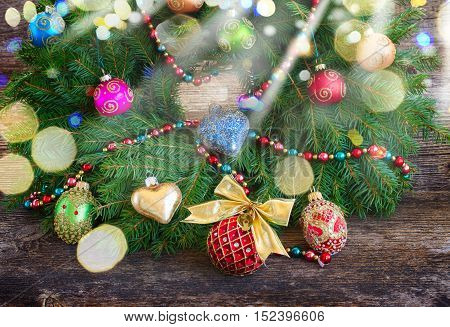 christmas decorated wreath on textured wooden background with glimming lights