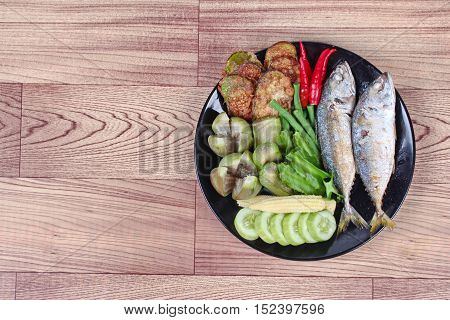Ready side dish served  for Thai spicy sour dip   as deep fired mackarels,boiled long-eggplant,lentils,winged bean ,red hot chili pepper and sliced cucumber on wood.  Have text space on left.